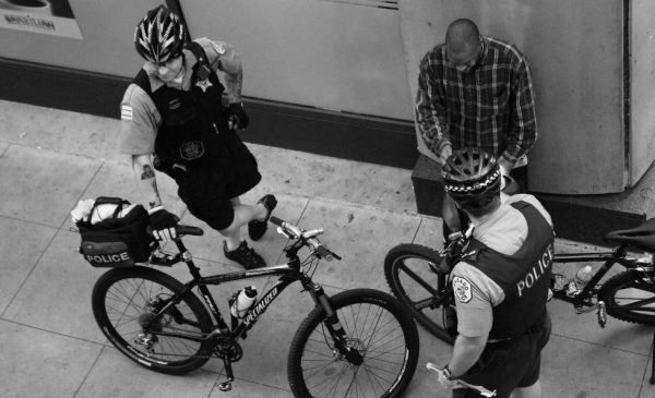 Two Chicago police officers, who have been on bikes, talk with a Black man standing on a street corner in downtown Chicago.
