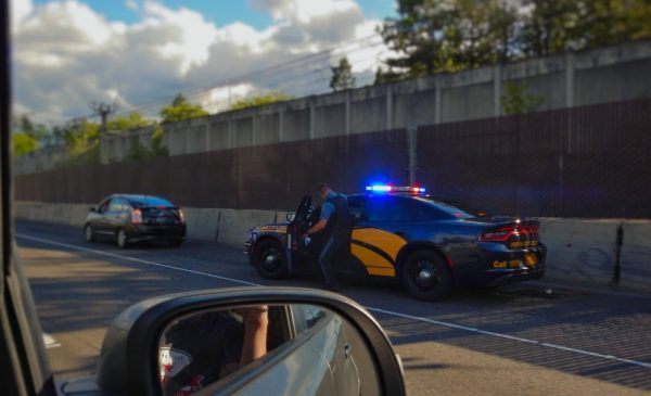 A police officer pulls over a driver on the side of a highway.
